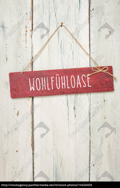 Rotes Holzschild Vor Weisser Holzwand Wohlfuhloase Lizenzfreies