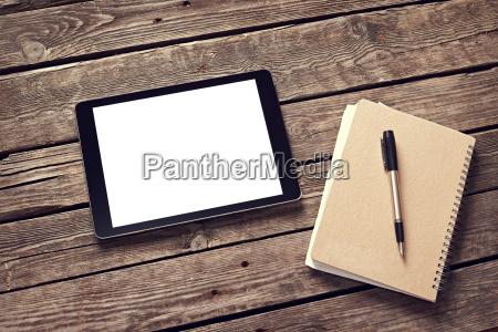 tablet und notizblock auf dem desktop