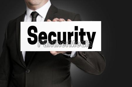 security schild wird von geschaeftsmann gehalten