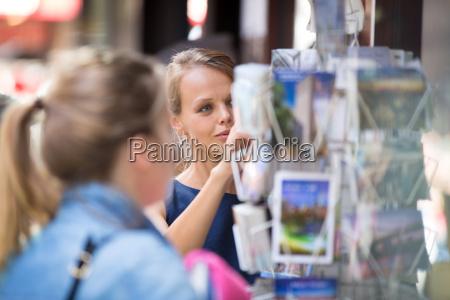 huebsche junge frau die eine postkarte