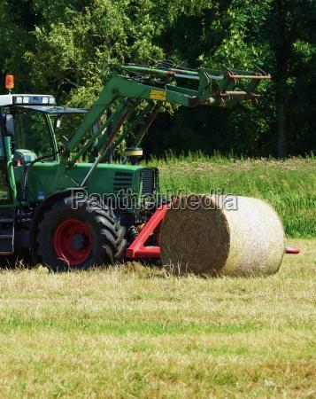 traktor mit einem strohballen auf einer