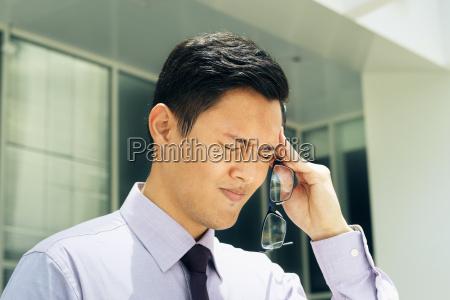 chinese man with eyeglasses suffers myopia