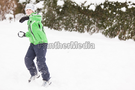 young boy enjoying a winter snowball