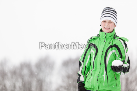 smiling young boy holding a snowball