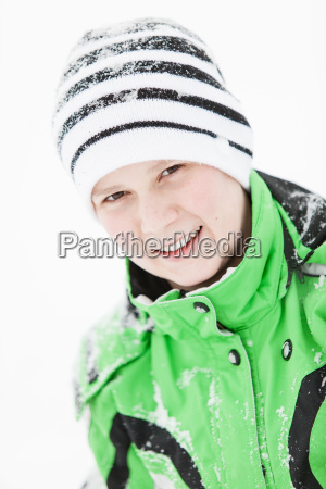 happy young boy sprinkled with winter
