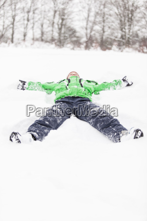 young boy lying stretched out in
