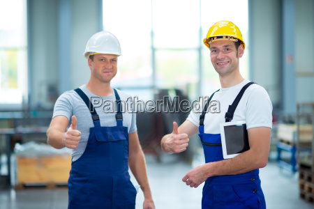 two worker in factory with thumb