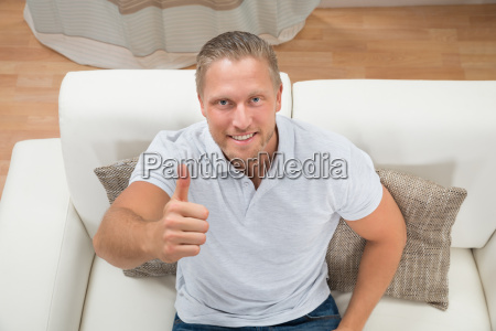 man on sofa showing thumbs up