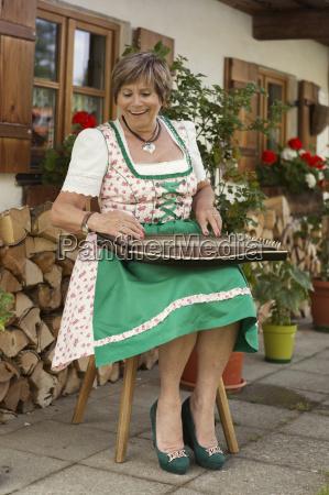 seniorin im dirndlkleid spielt zither