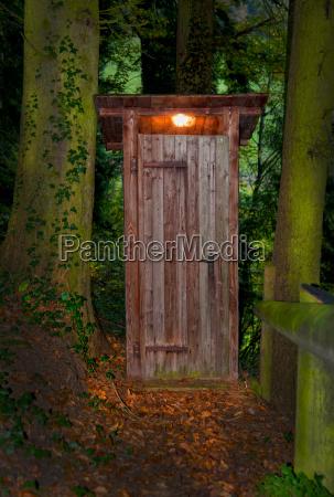 toilettenhaeusle mit beleuchtung im wald zwischen