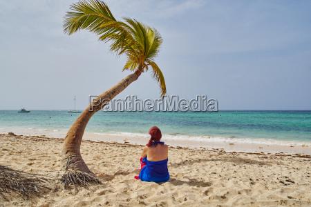 frau sitzt unter einer kokospalme