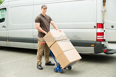 lieferung mann holding trolley mit kartonboxen