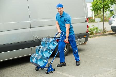 lieferung mann holding trolley mit wasserflaschen