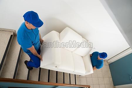 zwei movers tragen sofa auf treppe