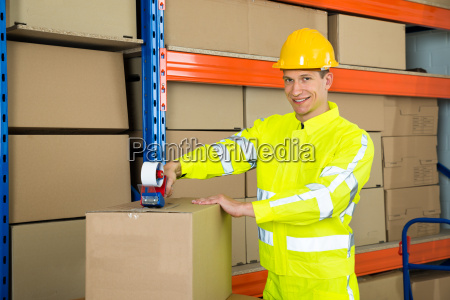 worker sealing cardboard box with adhesive