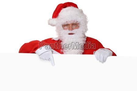 weihnachtsmann nikolaus mit bart zeigt an