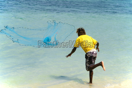 junger mauritianer wirft am strand ein