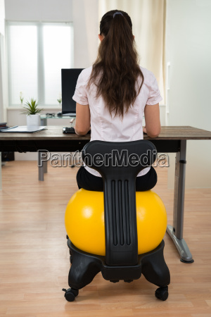 businesswoman sitting on fitness ball in
