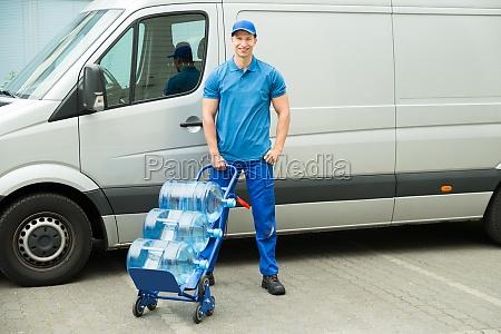 lieferung man holding trolley mit wasserflaschen