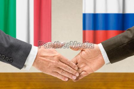 representative of italy and russia shake
