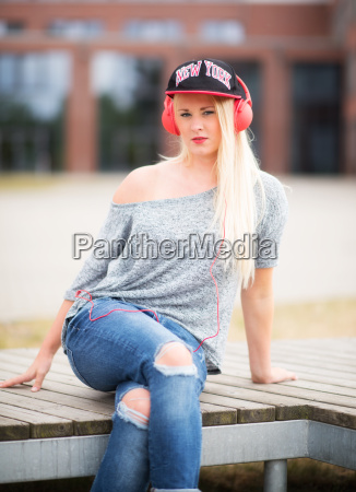 young woman in jeans sitting outside