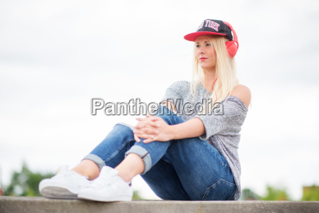 blonde girl sitting outside and listening