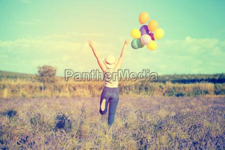 junge frau mit bunten ballons auf
