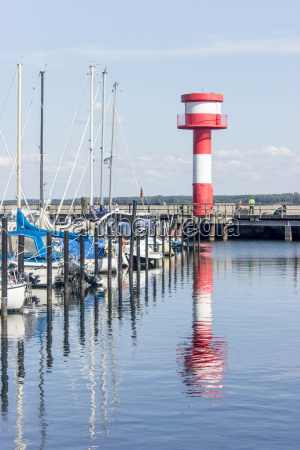 lighthouse and sailboats in the harbor
