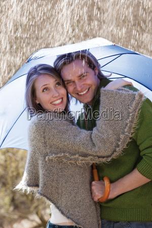 paar in der regen laechelnd