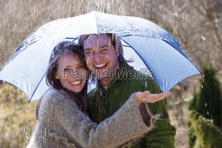 junge paare die spass im regen
