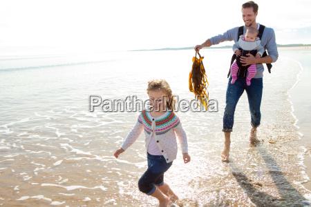 vater mit kindern auf dem strand