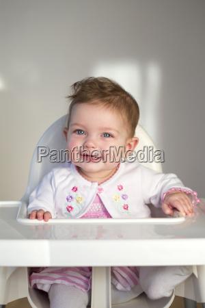 froehliches baby im hochstuhl
