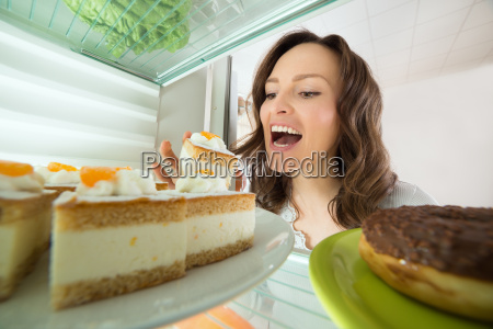 woman eating slice of cake from