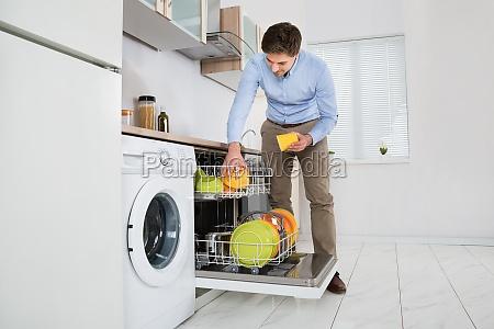 man putting geschirr in der spuelmaschine