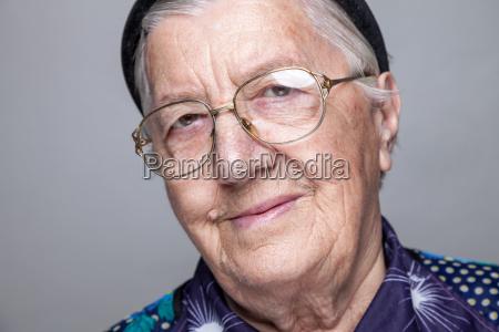 portraet einer aelteren frau mit brille