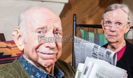 elderly man and woman with newspaper