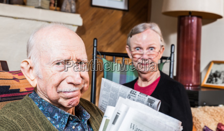 elderly husband and wife with newspaper