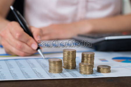businessperson with coins over graph and