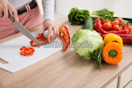 woman chopping chili pepper with knife