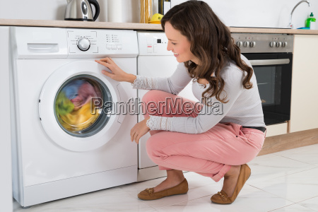 woman looking at clothes rotating inside