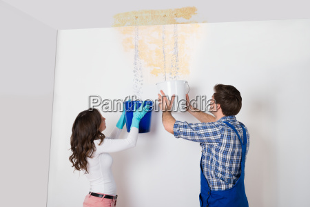 woman and repairman collecting water from