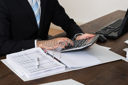 businessperson calculating invoice in office