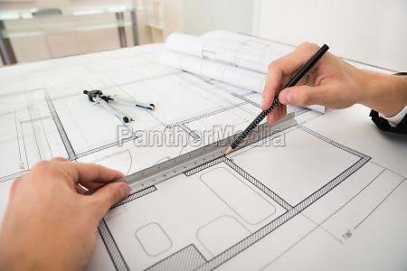 engineer drawing diagrams on blueprint paper