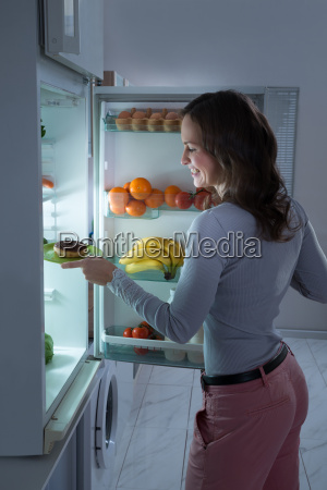 woman taking donut from refrigerator
