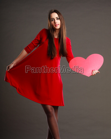 woman in red dress holds heart