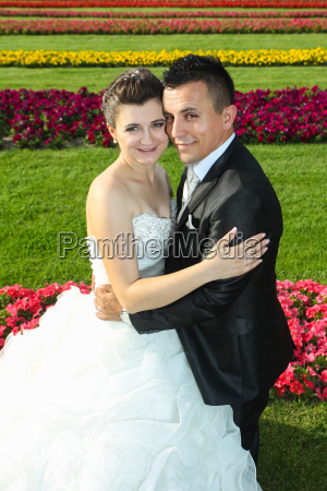 bride and groom posing on lawn