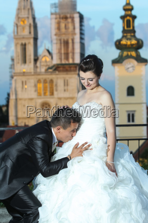 groom kissing bride on stomach
