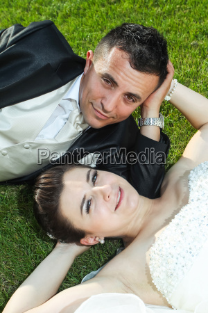newlyweds on grass looking at camera