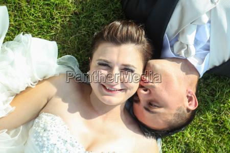 newlyweds kissing on grass