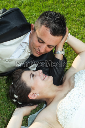 newlyweds on grass looking at each
